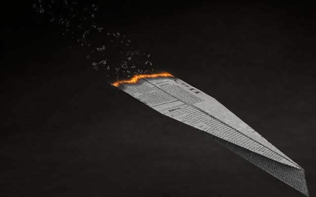Image of a paper plane, made out of newspaper, on fire