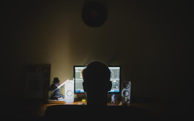 Shadowy figure at a computer