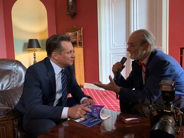 Photo of Krzysztof Szubert speaking to reporter